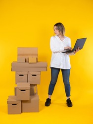 Logistics of parcel delivery. A woman with a laptop stands next to a lot of cardboard boxes. The business on the delivery of parcels. Home delivery service. Businesswoman prepares boxes for shipment.