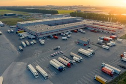 Logistics park with warehouse, loading hub and many semi trucks with cargo trailers standing at the ramps for load/unload goods at sunset.