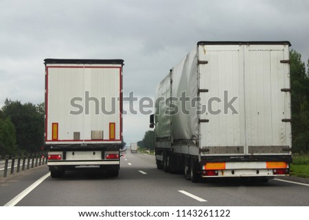 Logistics, shipping goods, road transportation is the van overtakes the truck transportation with tilt pricefrom on a two-lane asphalted country road in summer afternoon, rear view #1143261122