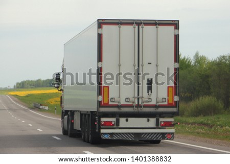 Logistics, shipping goods, road transportation - semi truck moving on a two-lane asphalted country road in summer day, side rear view #1401388832