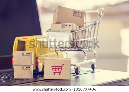 Logistics, supply chain and shipment service for e-commerce, online shopping concept : Boxes of goods, trolley, delivery van on a laptop computer, depicts customers uses internet to order  buy things