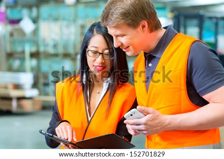 Logistics Teamwork Worker or warehouseman and his female coworker with tablet computer at warehouse of freight forwarding company