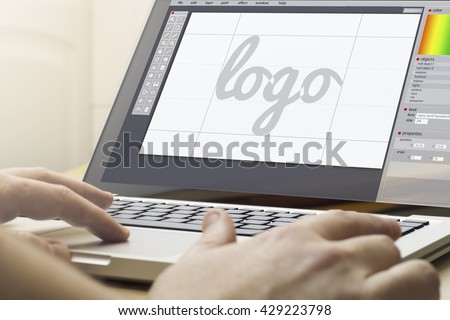 logo design concept: man using a laptop with logo design software on the screen. Screen graphics are made up.