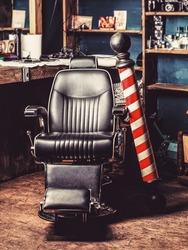 Logo of the barbershop, symbol. Stylish vintage barber chair. Hairstylist in barbershop interior. Barber shop chair. Barbershop armchair, salon, barber shop for men. Barber shop pole.