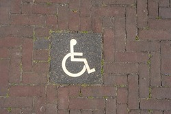 Logos for disabled on parking. handicap parking place sign on brick stones