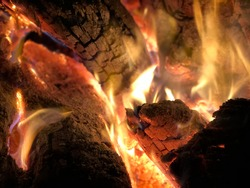 Logs aflame inside a campfire