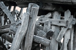 Logs of pillars of an old wooden bridge. Destroyed wooden old bridge. Building structure of a destroyed wooden bridge.