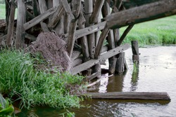 Logs of pillars of an old wooden bridge. Destroyed wooden old bridge. Building structure of a destroyed wooden bridge