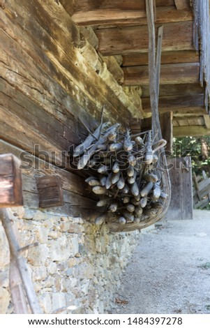 Logs stored in wooden construction hanging down from roof of old farmhouse made from wood and stones