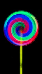 Lollipop toys  growt in the dark Consisting of green, red, blue and yellow handles spin, black background