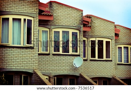 Lomofied Image of a Residential Complex with a Satellite Dish in the middle. (Intensionally Sharpened) - stock photo