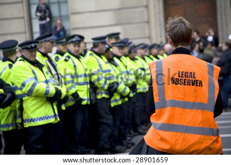 LONDON - APRIL 1 : A volunteer legal observer watches police conduct during G20 protests April 1, 2009 in London. 35,000 people join the demonstrator in Central London.