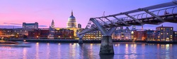 London at sunset, Millennium bridge leading towards illuminated St. Paul cathedral over Thames river with city bathing in electric light. Panoramic toned image.