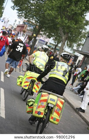 LONDON - AUG 30 : St John Ambulance aiders, bicycles allow to move more quickly through crowds with medical equipment, are ready to help patients at Notthing Hill Carnival on Aug 30, 2010, London, UK