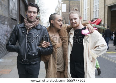 LONDON - August 27, 2016: a group of fashionably dressed men posing on background of the crowd on Broadway market. #555977302