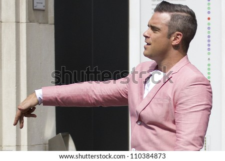 LONDON - AUGUST 17: Robbie Williams records the music video for his new song in Londons Spittalfields Market, August 17, 2012 in London, Uk - stock photo