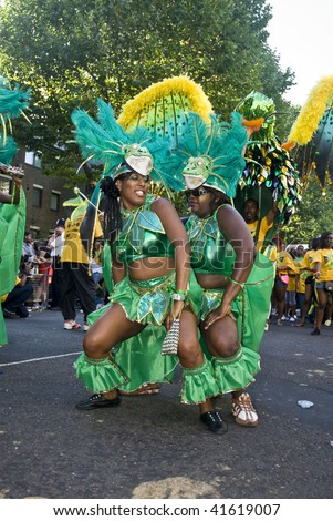 LONDON - AUGUST 31: Two girls in green costumes dancing with each other from the Jamaica Twist at the Notting Hill Carnival on August 31, 2009 in London, England.