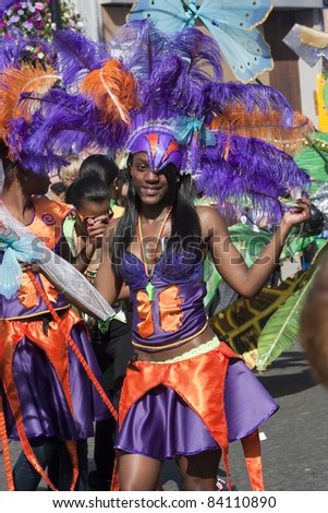 LONDON - AUGUST 29: Unidentified Jamaican girls in carnival costume, dance in parade during the Notting Hill Carnival on August 29, 2011 in Notting Hill, London, England.