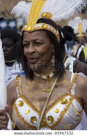 LONDON - AUGUST 29: Unidentified old Jamaican woman in carnival costume, walks during the Notting Hill Carnival on August 29, 2011 in Notting Hill, London, England. - stock photo