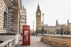 London - Big Ben tower and a red phone booth . Telephone box empty streets