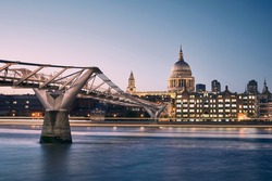 London cityscape at dusk. City waterfront with Millennium Footbridge against St. Pauls Cathedral. United Kingdom.