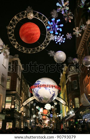 LONDON - DECEMBER 16: Christmas Lights Display on Carnaby Street on December 16, 2010 in London, England. The modern colorful Christmas lights attract and encourage people to the street. - stock photo