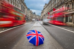 London, England - British style umbrella at busy Regent Street with iconic red double-decker buses on the move