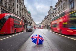 London, England - British style umbrella at busy Regent Street with iconic red double-decker buses and black taxies on the move