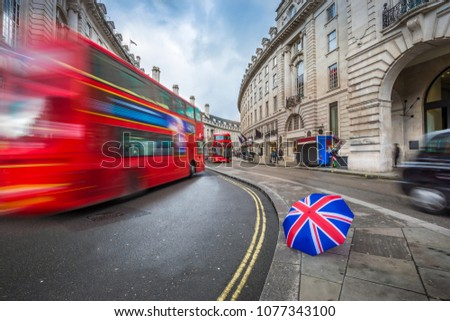 London, England - Iconic red double-decker buses and black taxi on the move on Regent Street with british-style umbrella stock photo