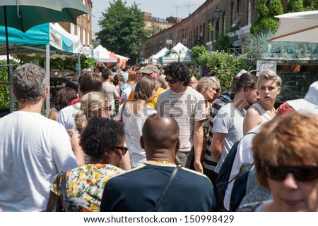 LONDON, ENGLAND - JULY 14:Crowd jostles its way along the bust road at the Columbia Road Flower Market in London, UK on July 14, 2013.