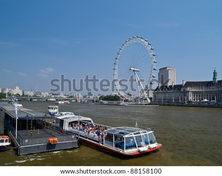 LONDON, ENGLAND - JULY 2: Millennium Wheel across the river Thames on July 2, 2009. The large ferris wheel was constructed in time for the Millennium celebrations in 2000 and now provides London views