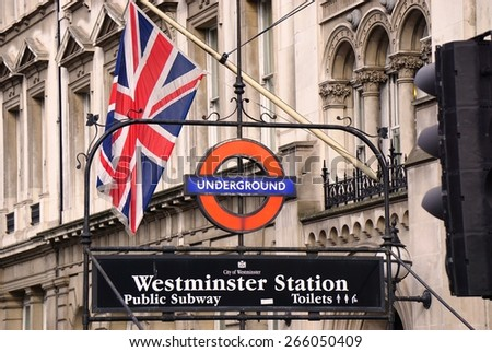 LONDON, ENGLAND -12 MARCH 2015- Editorial: Entrance sign for the London Underground (familiarly called the Tube) Westminster Station with a British flag.