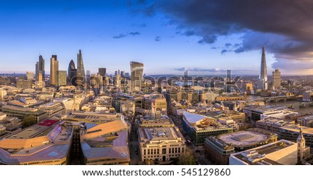 London, England - Panoramic skyline of the famous bank district of London, the leading financial district of the world at sunset with skyscrapers and dark clouds #545129860