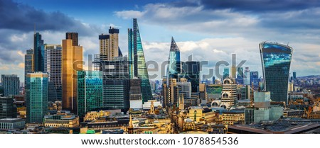 London, England - Panoramic skyline view of Bank and Canary Wharf, central London's leading financial districts with famous skyscrapers at golden hour sunset with blue sky and clouds #1078854536
