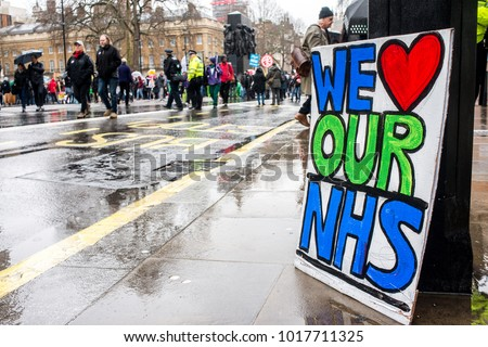 London, England. 3rd February 2018. EDITORIAL. WE LOVE OUR NHS poster sits in the rain at the NHS In Crisis demonstration through central London, in protest of underfunding & privatisation of the NHS.