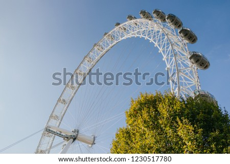 LONDON, ENGLAND - 25th October, 2018: London Eye cabins with a green tree, with blue sky background, in a sunny day in London, United Kingdom. #1230517780