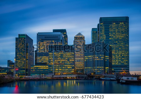 London, England - The skyscrapers of Canary Wharf, the famous financial district of London at blue hour #677434423