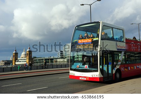 LONDON, ENGLAND, UK- JANUARY 10,2015: Tourist sightseeing bus parking on London Bridge under the cloudy sky in London, England, UK