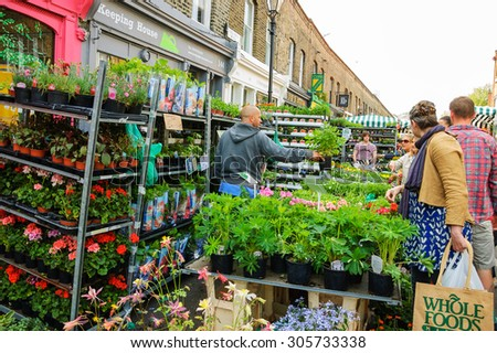 LONDON, ENGLAND, UK - MAY 4, 2014: People buying plants and  flowers at Columbia Road Flower Market. This London\'s principal flower market is opened every Sunday.