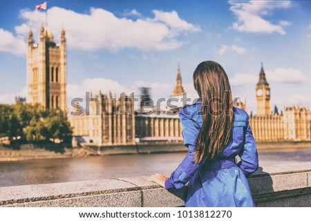 London Europe city autumn travel urban tourist woman in blue coat looking at Westminster and Thames river, famous tourism attraction landmark. Autumn season traveller people lifestyle. Wanderlust.
