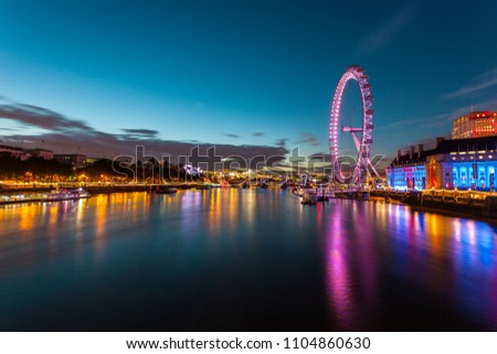 london eye at night with reflections.