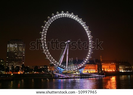 London eye - London landmark. Survey Wheel in night illumination over the Thames river