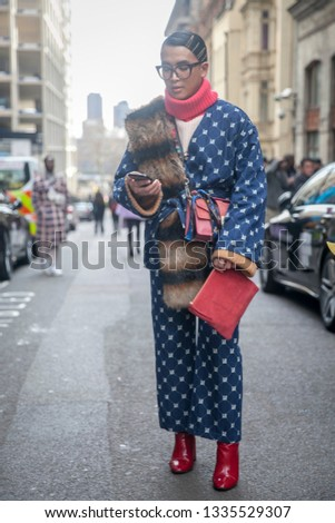 LONDON - FEBRUARY 17, 2019: Stylish attendees gathering outside 180 The Strand for London Fashion Week. A guest is seen wearing a blue suit and red boots #1335529307