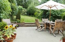 London garden in summer with patio, wooden garden furniture and a parasol or sun umbrella