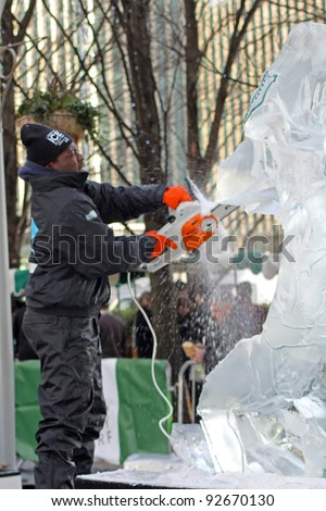 LONDON - JANUARY 13: A unidentified member of the African Ice Sculpting Team working on their Sculpture for the Annual London Ice Sculpting Festival, Canary Wharf, on January 13, 2012 in London, UK.