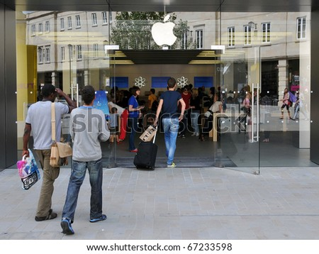 LONDON - JULY 28: Shoppers enter an Apple store as major retail group DSG International predict the electronics giant's iPad will become a Christmas best seller July 28, 2010 in London, UK. - stock photo