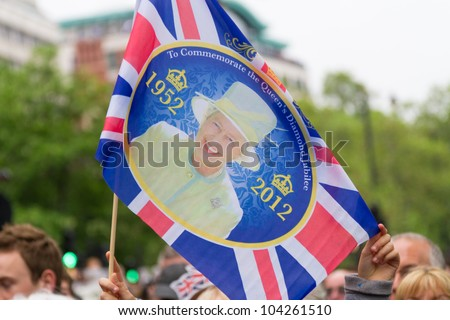 LONDON - JUNE 3: A commemorative flag is waved as crowds witness the Thames Diamond Jubilee Pageant on June 3, 2012 in London.