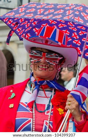 LONDON - JUNE 5: An unidentified woman dressed in red, white and blue, holding umbrella celebrates Diamond Jubilee celebrations on June 5, 2012 in London.