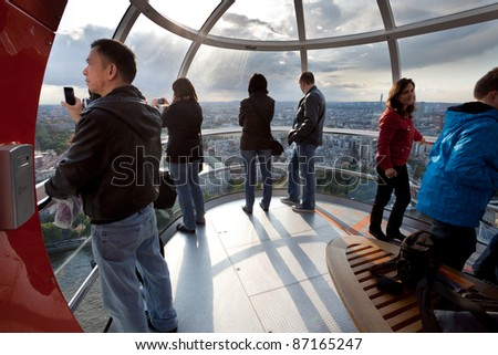 LONDON - JUNE 10: Unidentified tourists in London eye cabin observe the city from a bird's eye view on June 10, 2011 in London, UK. It's tallest Ferris wheel in Europe 135m (443ft) and most popular paid tourist attraction in UK