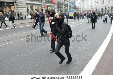 LONDON - MARCH 26: A breakaway group of protesters run along Regent Street during a large anti-cuts rally on March 26, 2011 in London, UK.